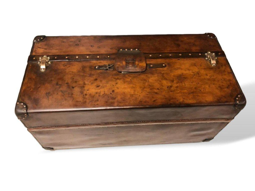 Lot 164   -  An early 20th century Louis Vuitton Malle Ideal trunk in natural cowhide leather.  Original lock, latches & pins.  Interior has been relined.  100cms wide x 48cms tall x 48cms deep.