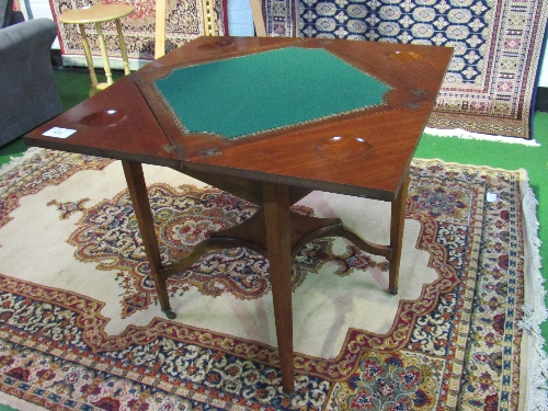 Lot 111 - Edwardian mahogany envelope-type card table with display shelf, on casters, 78cms x 78cms x 71cms