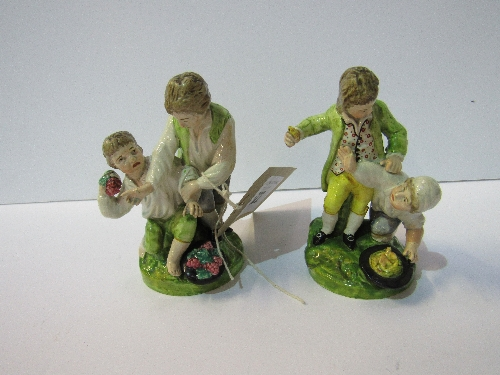 Lot 522 - Rare pair of 18th century Staffordshire figures, 2 boys fighting over fruit (tip of thumb missing on one)