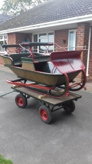 Lot 11 - SCANDINAVIAN SLEIGH finished in natural varnished wood with green/red paintwork, on red and black runners. Seats four passengers - two rows of forward facing seats, curved dash board and rein rail. Comes with shafts