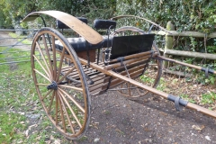 Lot 10 (1) - MEADOWBROOK CART to suit 16 hh; a relatively modern vehicle, possibly Amish, with hickory body, wheels and shafts in natural varnish finish. On 55ins wheels with elliptic springs and curved mud guards. Black leatherette seating, with one side lifting for access. Fitted with rein rail and whip holder