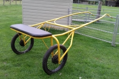 Lot 12 - SULKY to suit 13.2 to 15 hh; metal frame painted red, synthetic bench seat and pneumatic tyres. Photo shows a duplicate Sulky in yellow