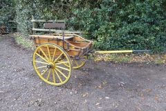 Lot 5 (1) - MARKET CART to suit 12 to 13 hh pony; in natural varnished wood on a yellow undercarriage. On 14-spoke Warner wheels with semielliptic springs and a cranked axle. It has a rear drop-down tailboard, hand brake and whip holder. One of the shafts has broken off but is still with the vehicle