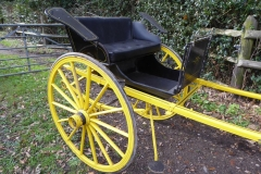 Lot 8 (1) - DENNETT GIG by McBride of Ballybay, to suit 14 to 15 hh; painted dark blue with yellow lining, supported on a yellow undercarriage with 14-spoke Warner wheels lined in dark blue, and Dennett springs. Buttoned leatherette seating, tilted mud guards, metal steps and lamp brackets