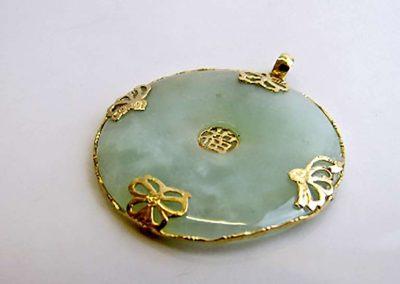 Lot 320 - 14ct gold mounted circular jade pendant
